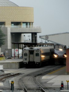 Amtrak locomotive and NJ Transit rolling stock in front of Gateway Plaza at LA Union Station